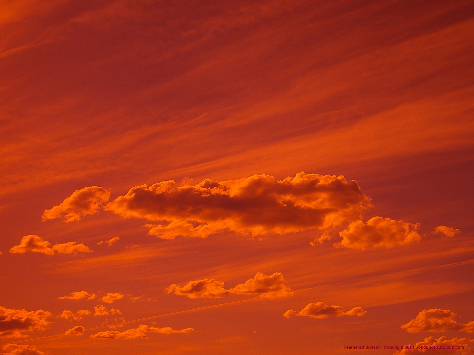 A rose colored sunset with cumulus and high altitude feathered clouds.